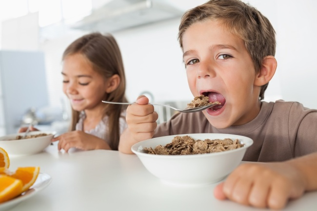 Boy eating cereal while having breakfast with his sister in the kitchen