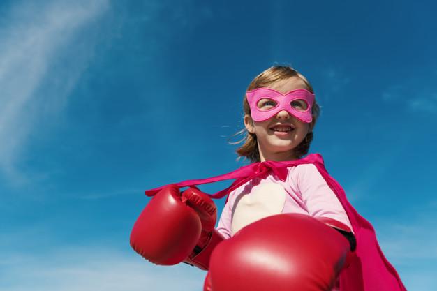 Little cute girl playing superhero